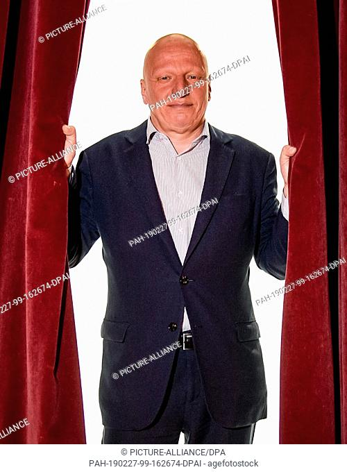 27 February 2019, Hamburg: Sewan Latchinian, new artistic director of the Hamburger Kammerspiele, looks through the curtain of the theatre stage during a photo...