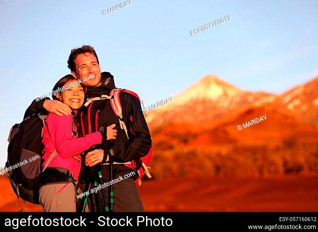 Happy couple hiking enjoying looking at view embracing in love. Hiker man and woman wearing backpacks enjoying sunset during hike on mountain volcano Teide