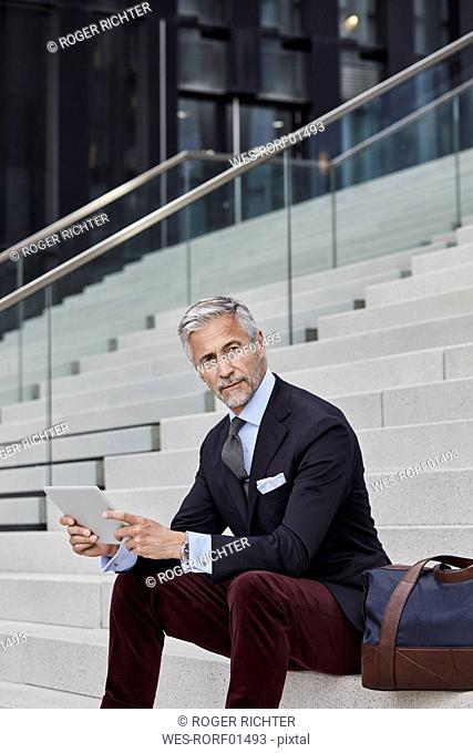 Portrait of fashionable businessman with travelling bag and tablet sitting on stairs