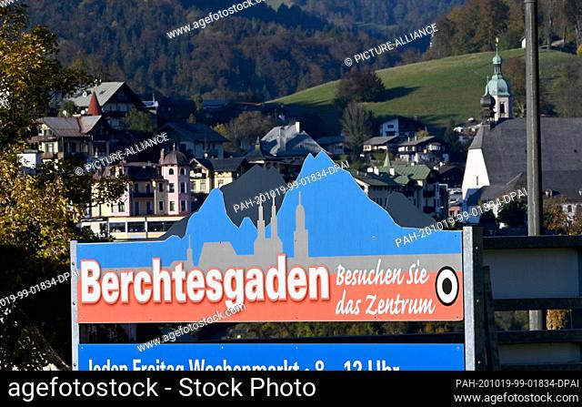 "19 October 2020, Bavaria, Berchtesgaden: A sign with the inscription """"Berchtesgaden - Visit the centre"""" hangs in front of the backdrop of the village"