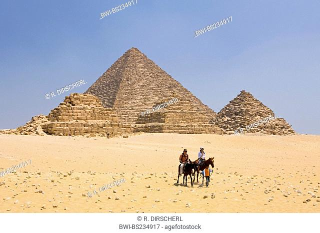 Pyramid of Menkaure and three small Pyramids of Queens with tourists on horses, Egypt