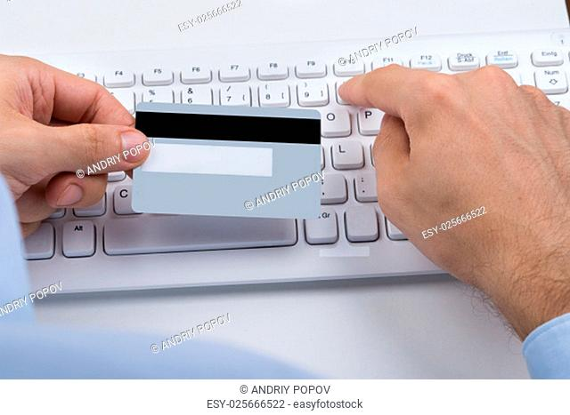 Close-up Of Hands Holding Credit Card On A Computer Keyboard
