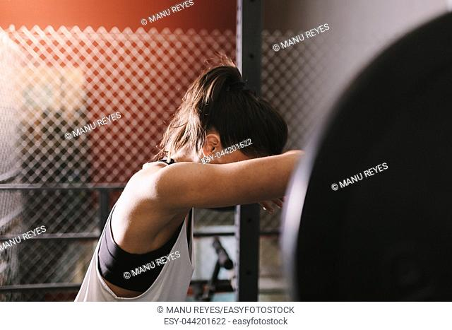 Athletic young woman concentrates before to do some weightlifting exercises