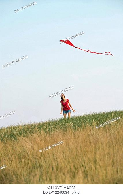 A young woman looking up at a red kite