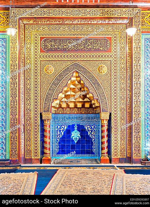 Golden ornate arched mihrab (niche) with floral pattern, blue Turkish ceramic tiles and arabic calligraphy at the public mosque of The Manial Palace of Prince...
