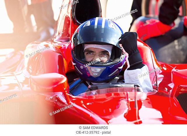 Formula one race car driver in helmet gesturing, celebrating victory