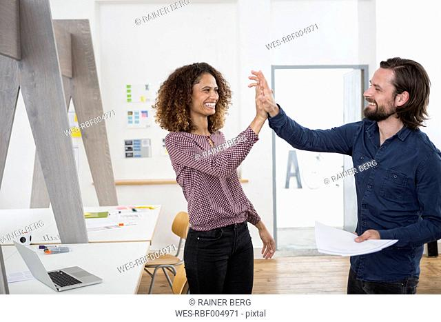 Two happy colleagues in office high fiving