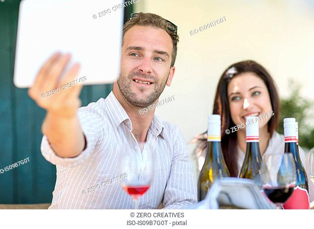 Couple taking selfie with digital tablet at outdoor lunch