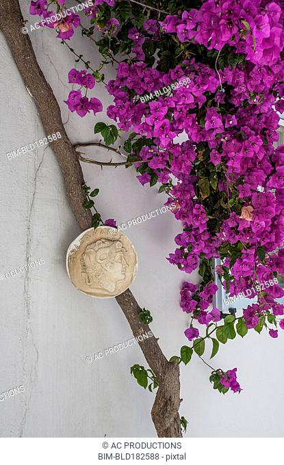 Sculpture and flowers on building exterior
