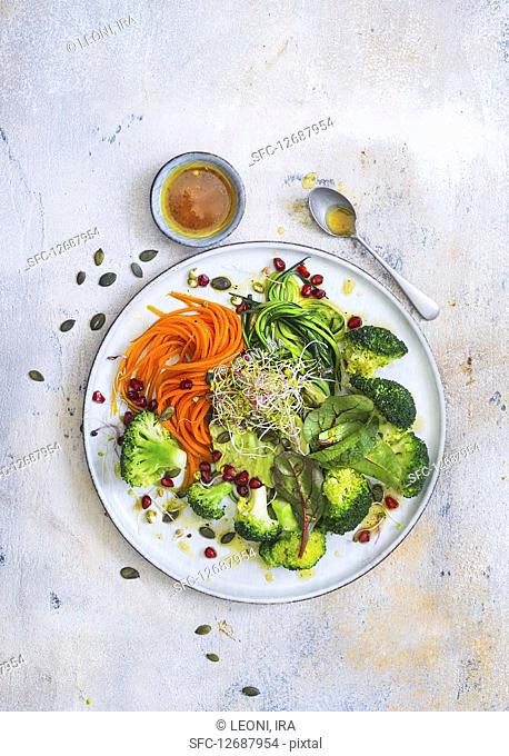 Vegan vegetable spaghetti with avocado, broccoli sprouts and pomegranate seeds