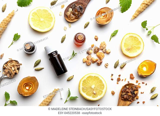 Bottles of essential oil with frankincense, cardamon, melissa, fresh lemon and other ingredients on a white background
