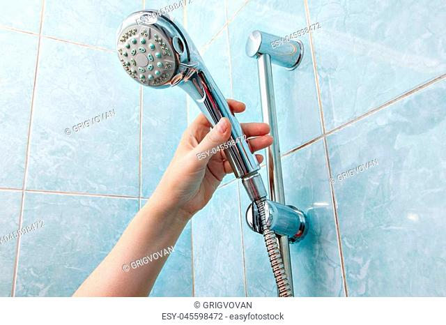 Replacing the plumbing in the bathroom, close-up wall mounted hand shower and hose holder with height adjustable bar slider rail