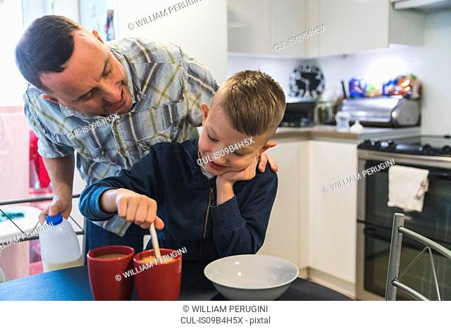 Father and son in kitchen, son stirring hot drink