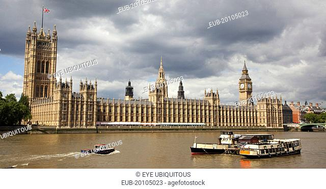 View across the river Thames from the Albert Embankment toward the Houses of Parliament. Dramatic clouds