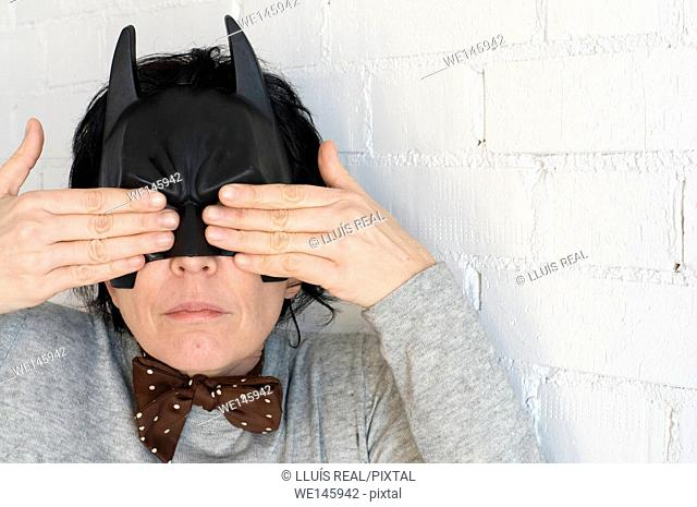 Young woman with a Batman mask and expression of a notty girl and with the hands covering her eyes