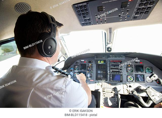 Caucasian pilot working in airplane cockpit