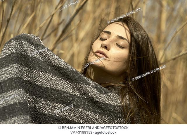 Young woman in undergrowth, wrapped in towel. Crete, Greece