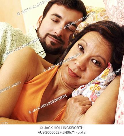 Portrait of a mature woman with a mature man sleeping behind her