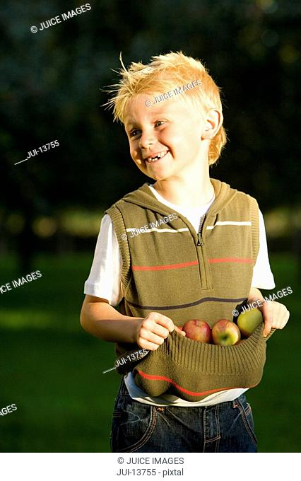 Boy 7-9 using top to collect apples, smiling