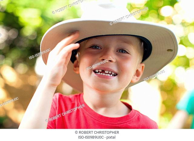 Boy in hat on sunny day in forest
