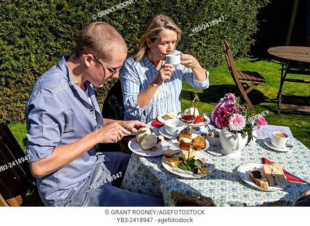 A Family Enjoy A Traditional English Afternoon Tea, Glynde, Sussex, UK