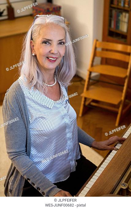Portrait of smiling woman playing piano at home