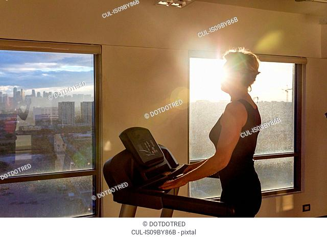 Woman walking on treadmill in gym facing city view, Manila, Philippines