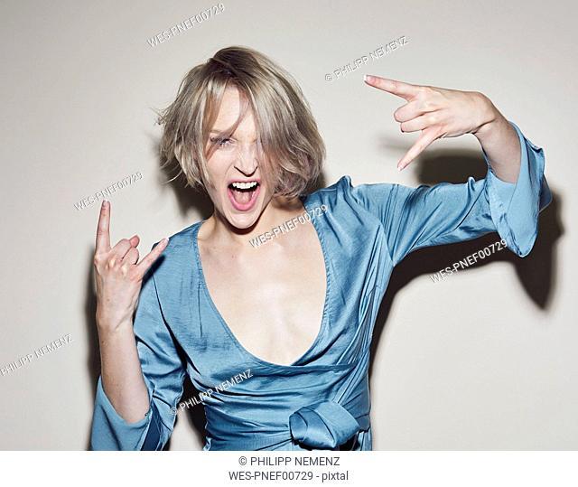 Portrait of blond woman wearing evening dress gesturing