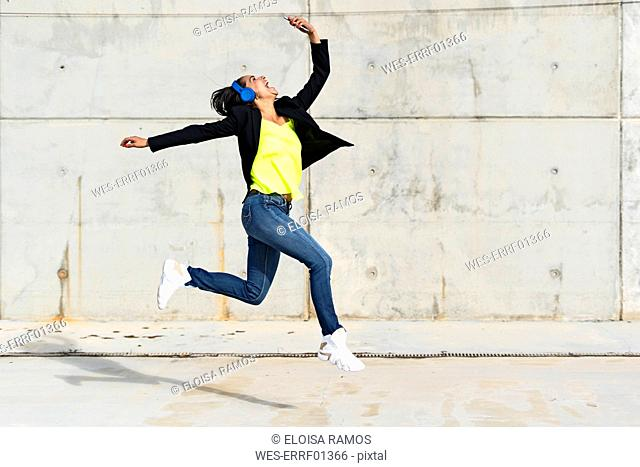 Woman with blue headphones listening music, jumping in the air and taking a selfie