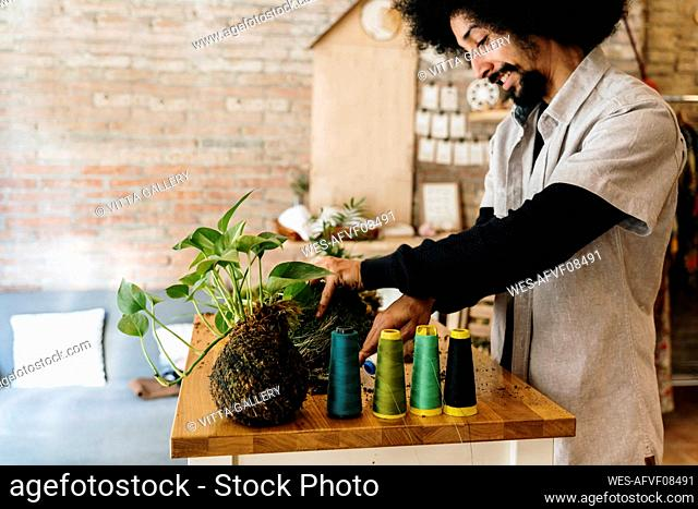 Man with kokedama plant and spools on table at home
