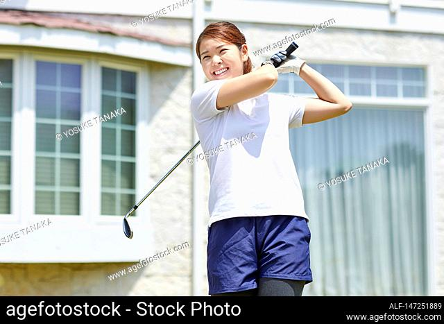 Japanese woman practicing golf in the garden