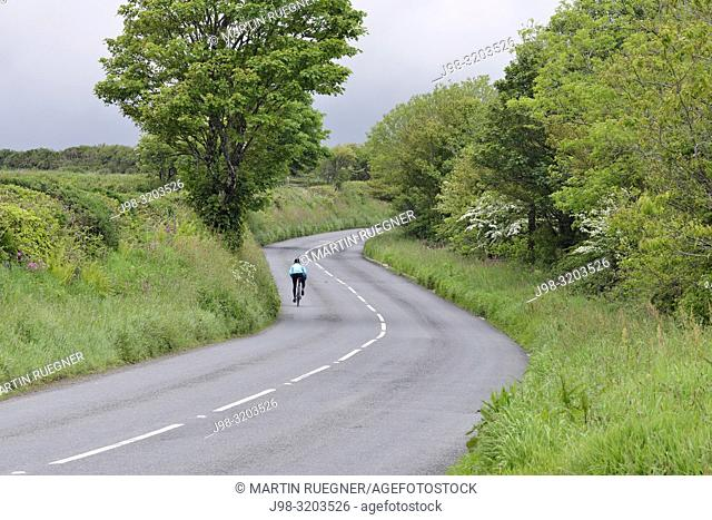 Country road with cyclist. Cornwall, England, UK