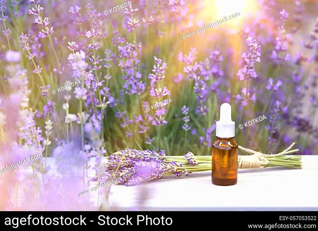 Essential lavender oil in the bottle with dropper on the table in lavender field. Horizontal close-up