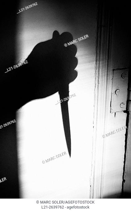 Silhouette of a hand holding a knife on a wall