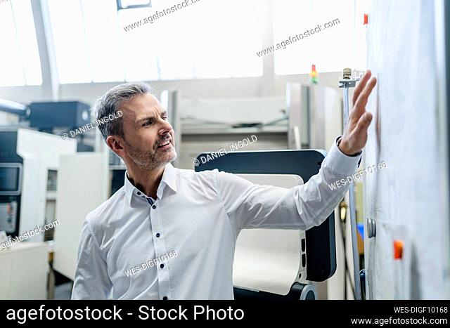 Businessman looking at plan in a factory