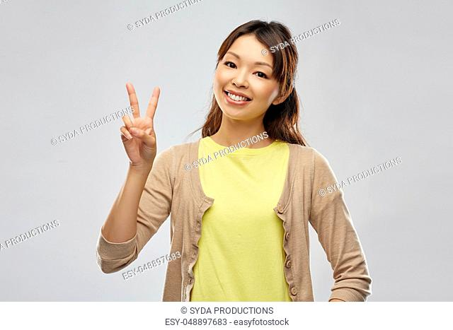 happy asian woman showing peace