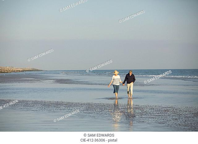 Mature couple holding hands walking in sunny ocean beach surf