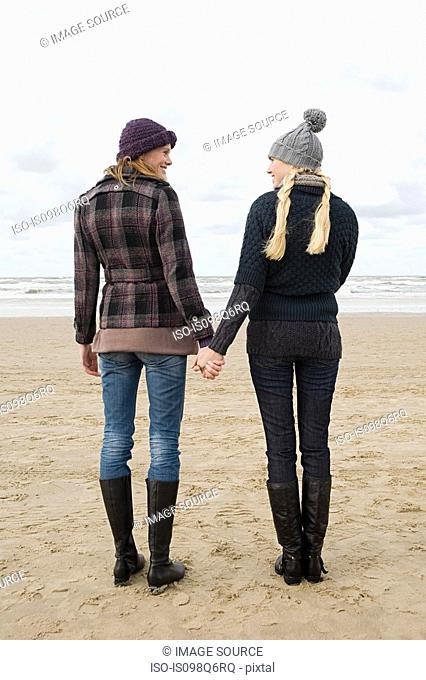 Women holding hands by the sea