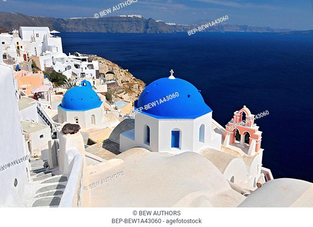 Greek white churchs with blue domes overlooking the sea, Oia, Santorini, Cyclades Islands, Greece