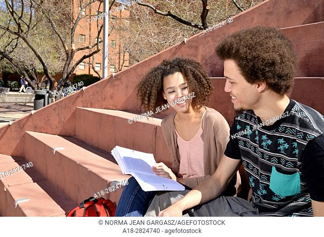 A young woman and man with books and electronics on a college campus