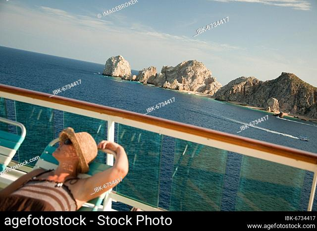 Beautiful woman relaxes on a cruise ship deck at land's end in cabo san lucas, Mexico, Central America