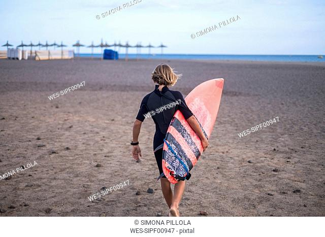 Spain, Tenerife, boy carrying surfboard on the beach