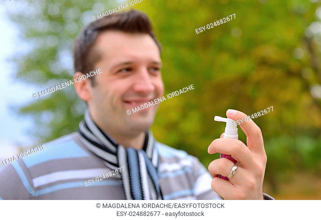 Young man using throat spray in cold season