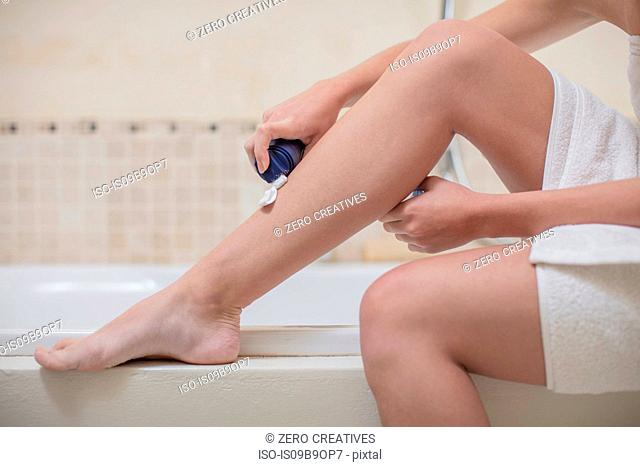 Young woman applying shaving foam to leg in bathroom, cropped