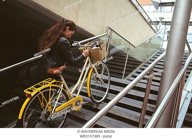 Woman with bicycle climbing up the stairs