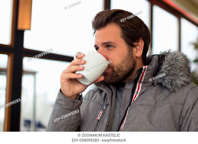 Thoughtful man wearing warm winter jacket looking out the window and drinking coffee