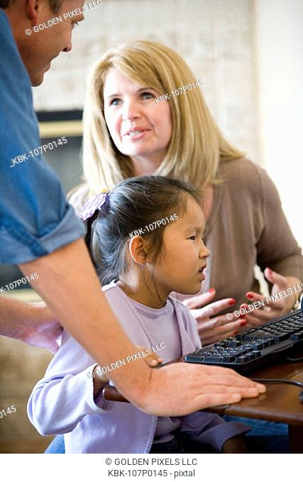 Parents with daughter working on a computer