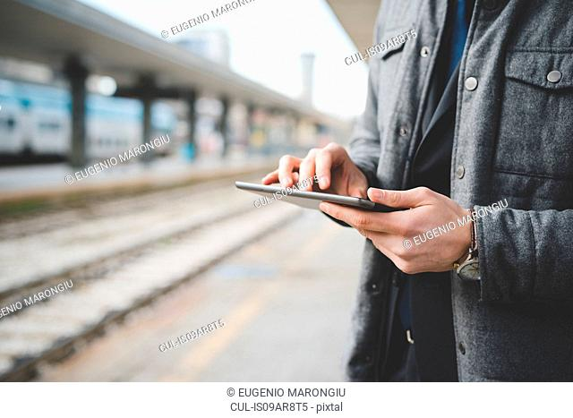 Cropped image of a young businessman commuter 's hands using digital tablet at train station