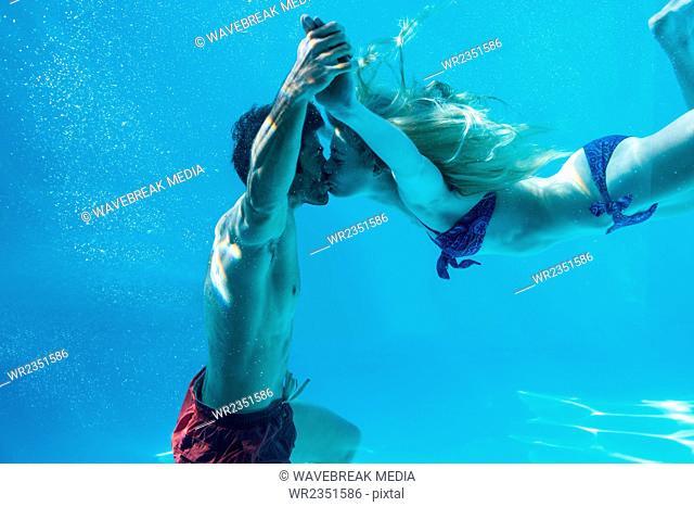 Happy couple kissing underwater