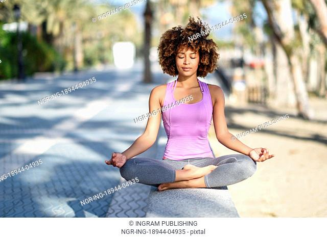 Black woman, afro hairstyle, doing yoga in the beach with eyes closed. Young Female wearing sport clothes in lotus figure with defocused background
